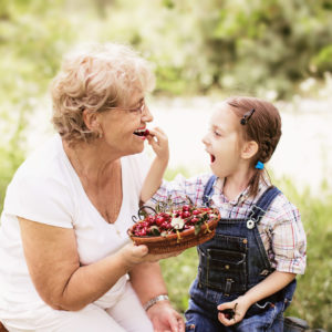 granddaughter is feeding her grandmother with cherries in the garden